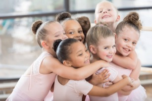 Young ballerinas form a smiling group hug
