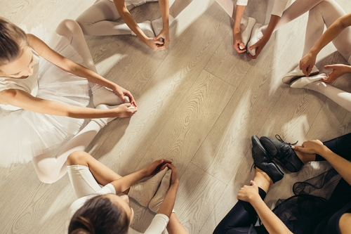 This image shows young ballerinas stretching while seated in a circle. Tailoring your classes to different audiences and genres is one of our top tips for dance studio owners.