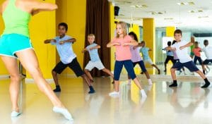 This feature image show a group of dance students practicing with a dance teacher.