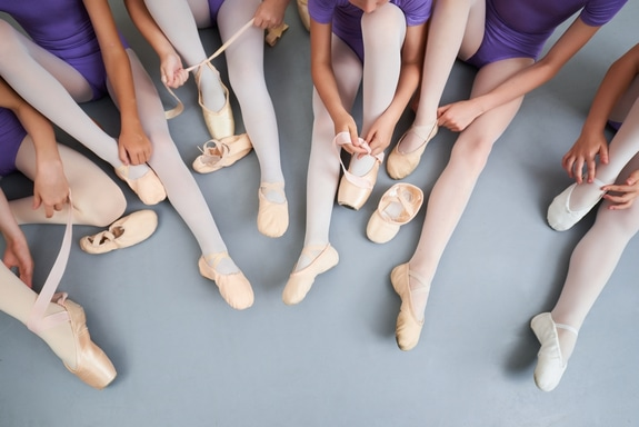 This image shows ballet dancers putting on their ballet slippers.